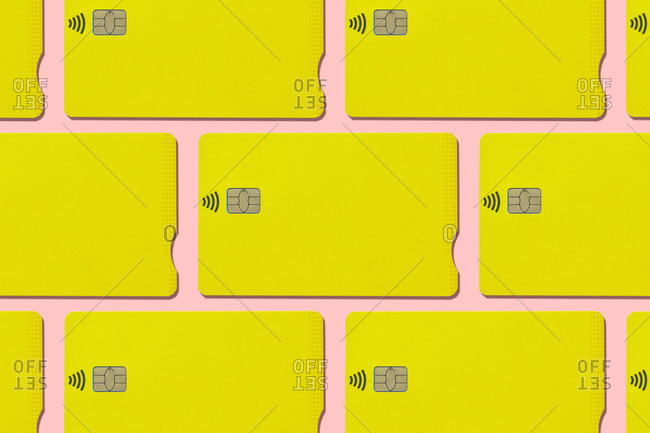 Yellow contactless credit cards pattern on pink background