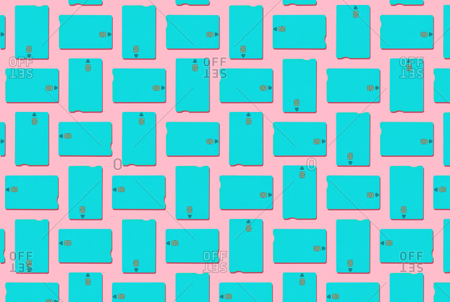 Blue contactless credit cards pattern on pastel pink background