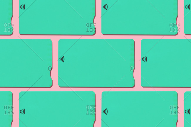 Mint green contactless credit cards pattern on pastel pink background
