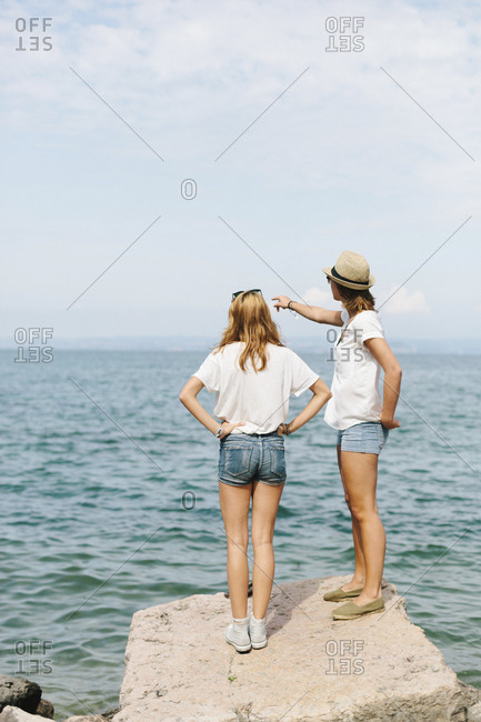 Two female friends standing at the lakeside- Lake Garda- Italy