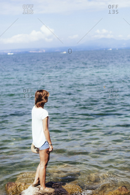 Young woman standing at the lakeside- Lake Garda- Italy