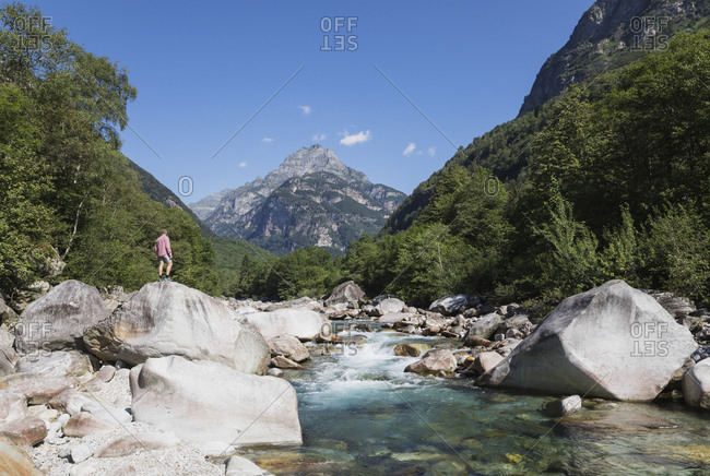 Man standing on rock at Verzasca river- Verzasca Valley- Ticino- Switzerland