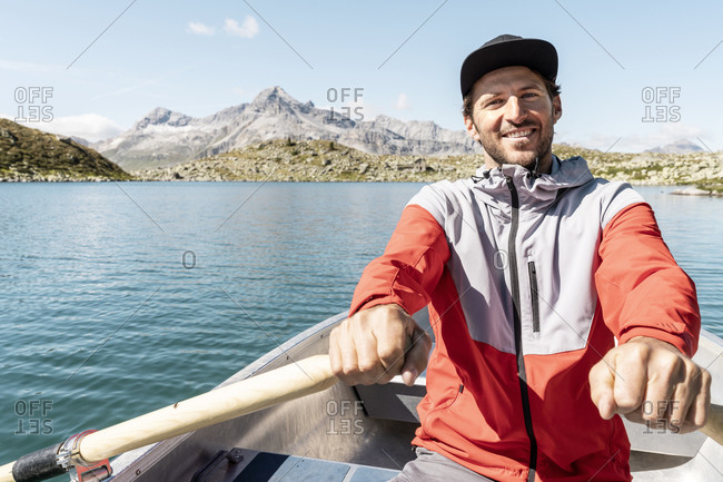 Young smiling man in a rowing boat- Lake Suretta- Graubuenden- Switzerland