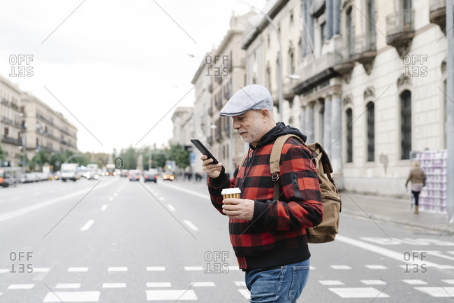 Senior man with backpack and coffee to go looking at cell phone while crossing the street- Barcelona- Spain