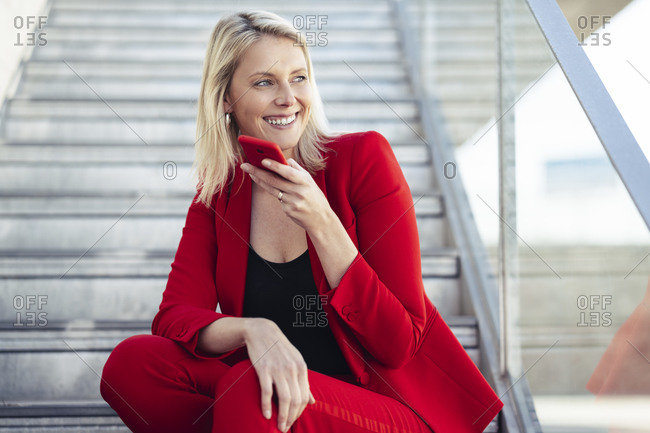 Blond businesswoman wearing red suit and using hands free telephone- sitting on stairs