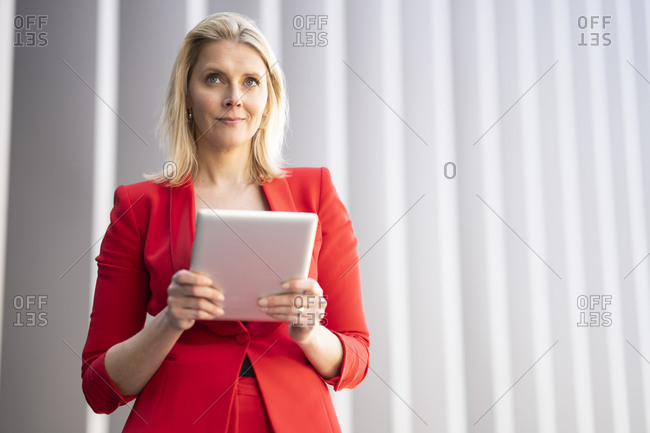 Blond businesswoman wearing red suit and using digital tablet