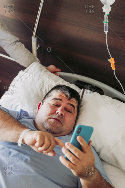 Patient lying in hospital bed using cell phone