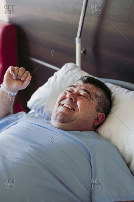 Portrait of smiling patient lying in hospital bed