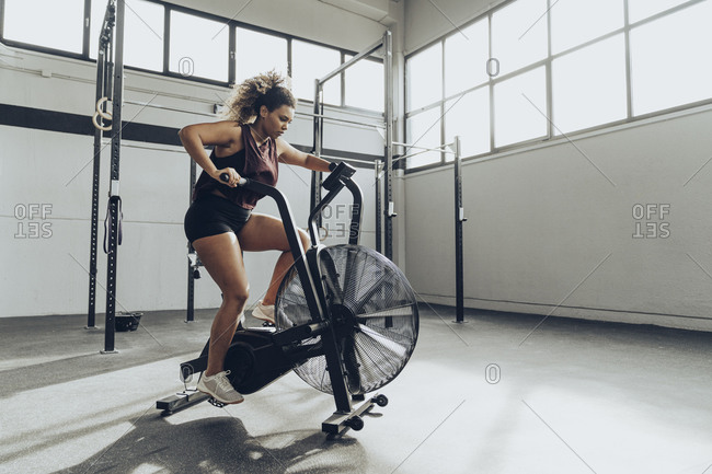 Young woman doing air bike workout in gym