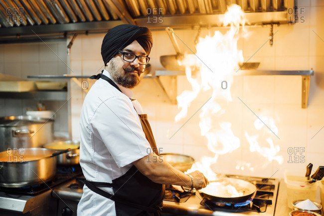 Indian chef flaming food in restaurant kitchen