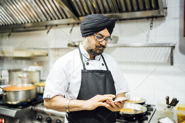 Indian chef using smartphone in restaurant kitchen