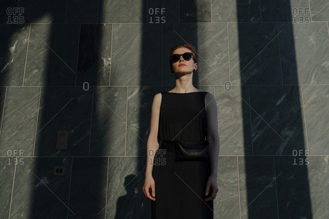 Red-haired woman with sunglasses- in front of stone wall with shadows