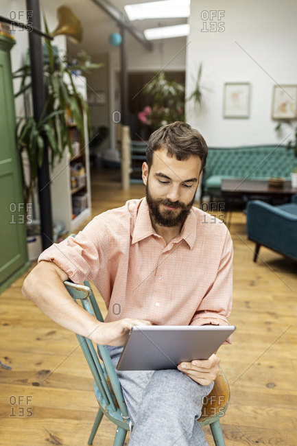 Young man sitting on chair- using digital tablet
