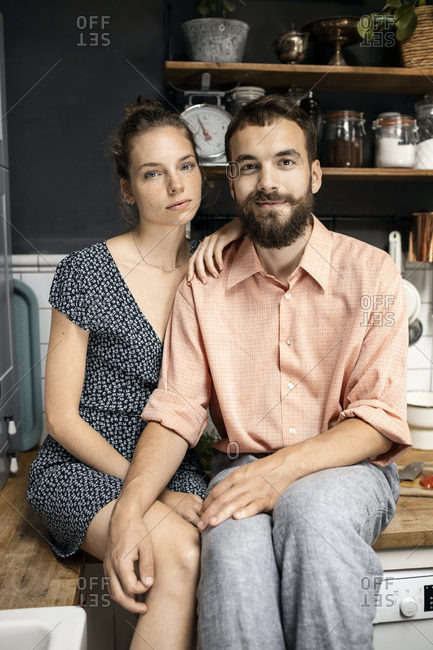 Young couple sitting on kitchen worktop- smiling