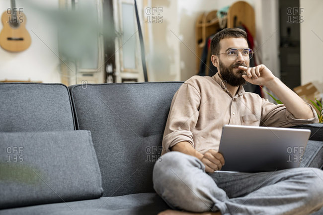 Young man sitting at home on couch- using digital tablet