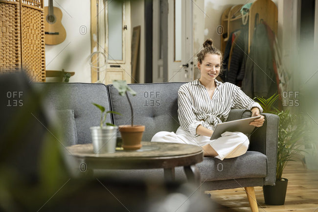 Young woman sitting at home on couch- using digital tablet
