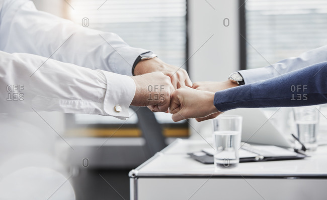 Team of business people fist bumping in office