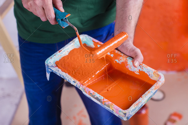 Close-up of man holding paint tray with orange paint