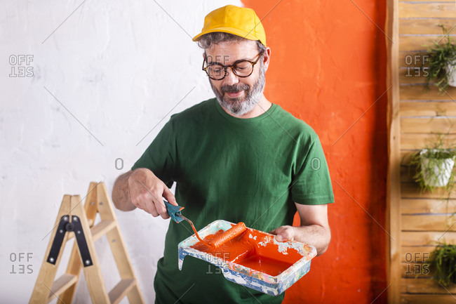 Smiling man holding paint tray with orange paint