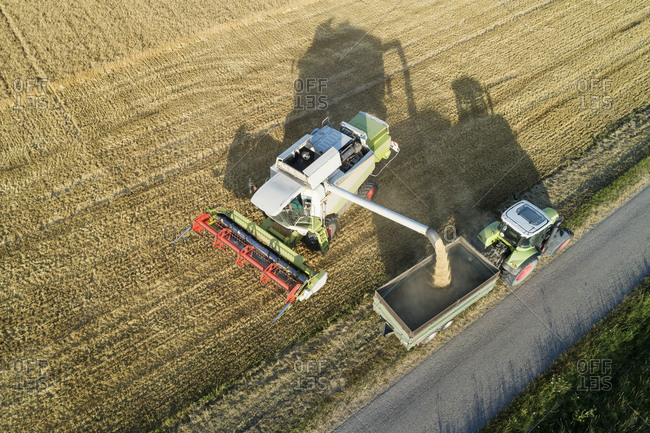 Germany- Bavaria- Drone view of combine harvester unloading grain on tractor
