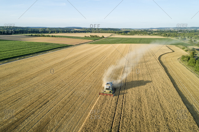 Germany- Bavaria- Drone view of combine harvester working in field