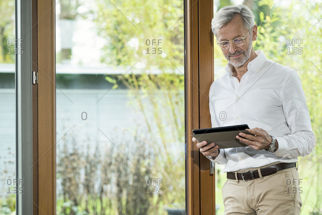 Senior man with grey hair in modern design living room standing at window using tablet