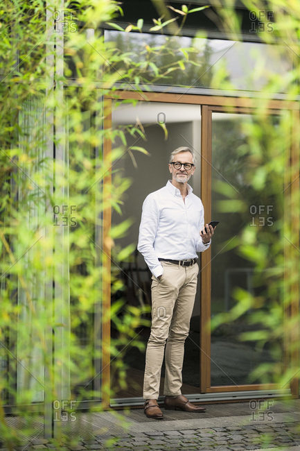 Senior man with grey hair holding smartphone in front of his modern design home in bamboo garden