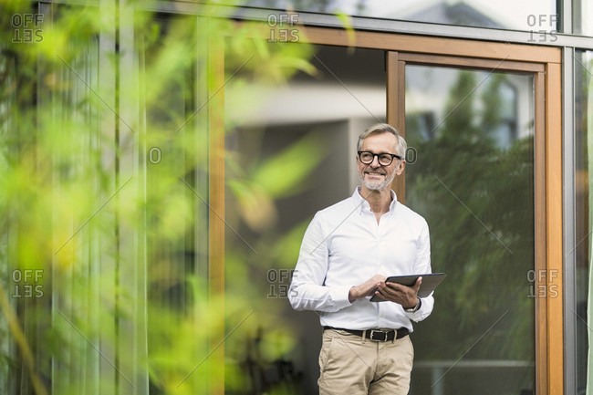 Smiling senior man with grey hair holding tablet in front of his modern design home in bamboo garden