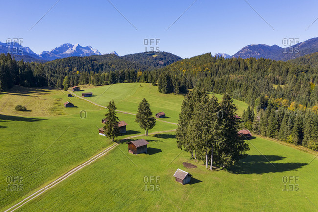 Germany- Bavaria- Krun- Drone view of huts standing at edge of springtime forest with Wetterstein Mountains in background