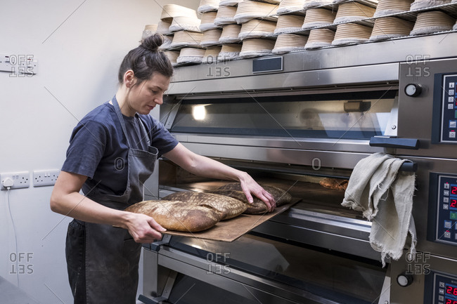Woman wearing apron standing in an artisan bakery, taking freshly baked loaves of bread out of oven.