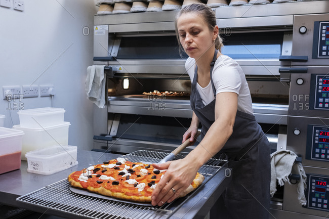 Woman wearing apron standing in an artisan bakery, preparing pizza to go into the oven.