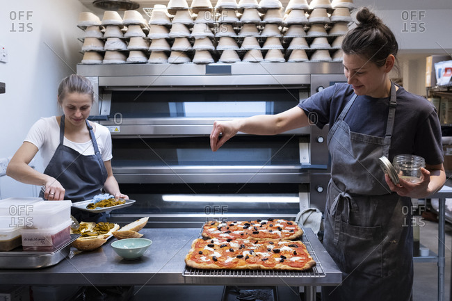 Woman wearing apron standing in an artisan bakery, preparing pizza.