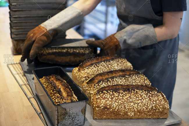 Close up of person wearing oven gloves placing freshly baked seeded loaves of bread on a tray in an artisan bakery.