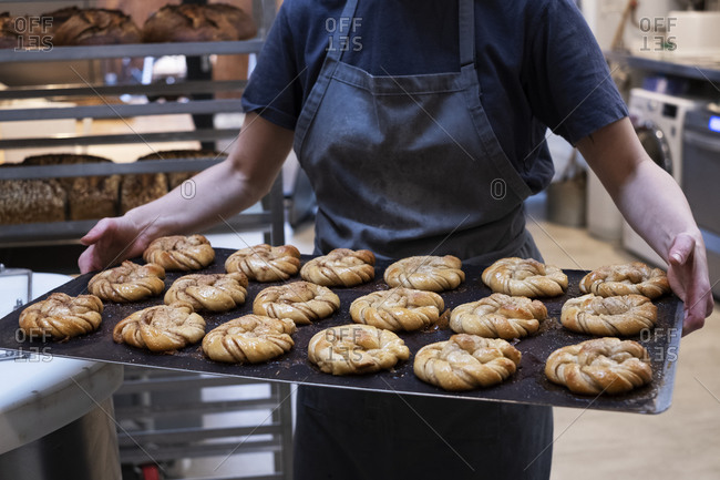 Close up of person holding tray with freshly baked cinnamon buns in an artisan bakery.