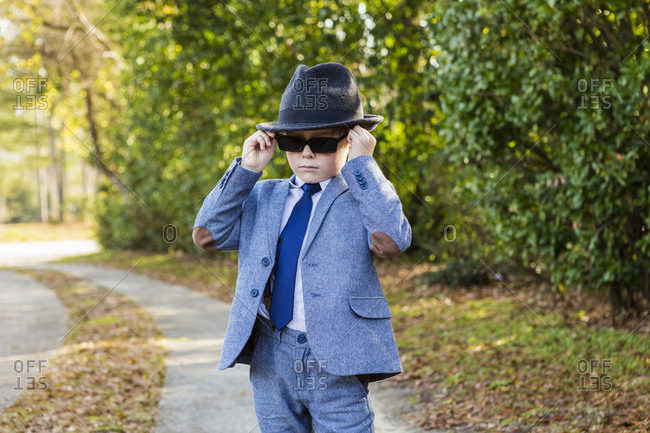 A six year old boy dressed in suit and wearing fedora, in driveway