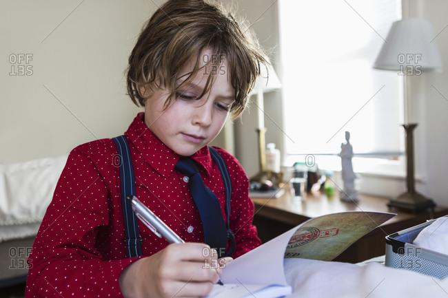 A six year old boy drawing on sketch pad