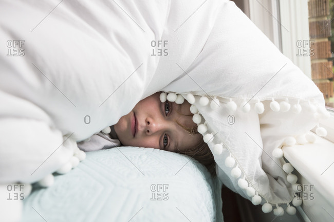A six year old boy in bed with covers over his head