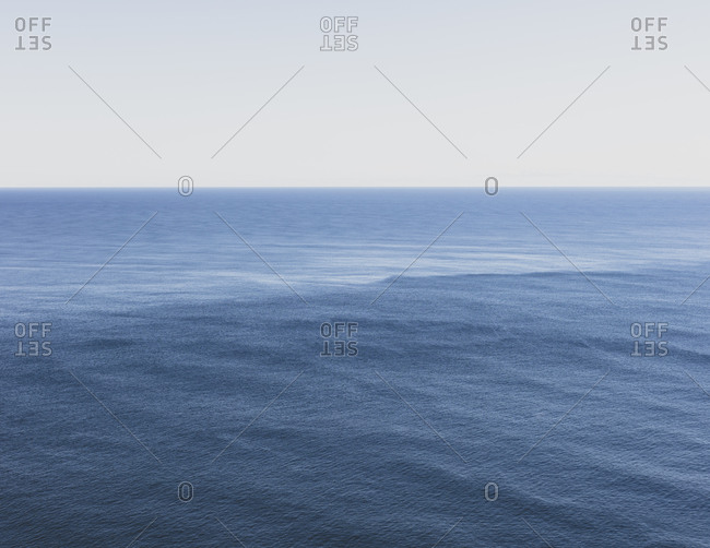 View of expansive ocean, horizon and sky at dusk