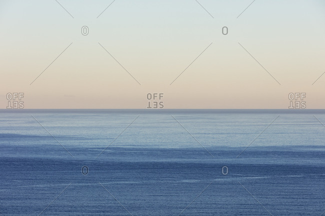 View of calm ocean waters, horizon and sky at dawn