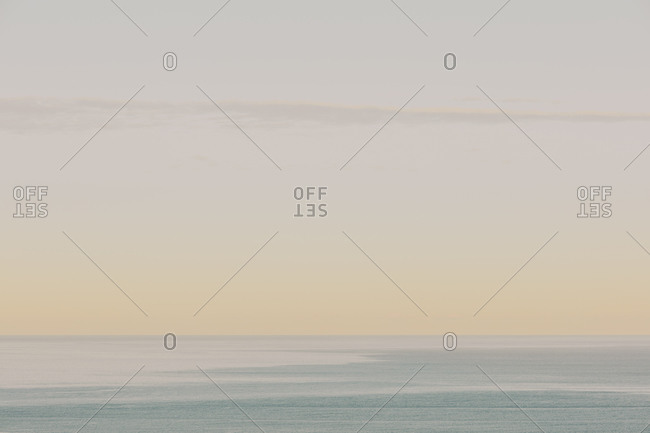 View of calm ocean waters, horizon and sky at dawn