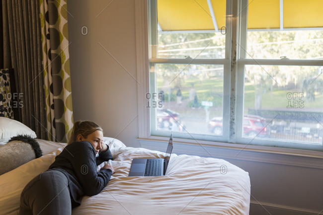 A thirteen year old teenage girl lying on bed watching her laptop