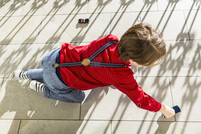A six year old boy playing with toy cars on terrace