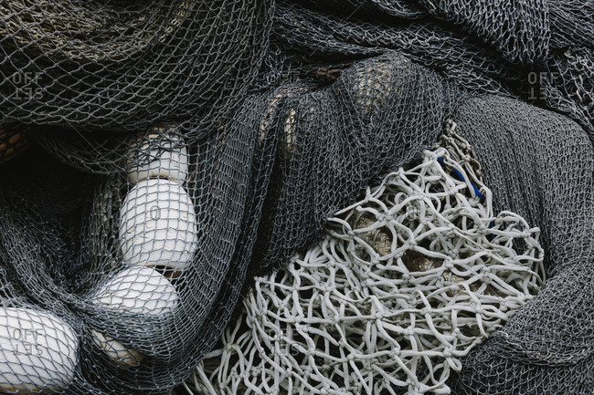 Pile of commercial fishing nets and gill nets on a fishing quay.
