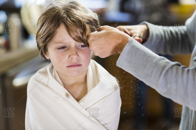 A six year old boy getting his hair cut at home by his mother
