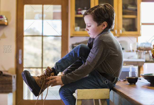 A six year old boy putting his boots on, sitting on a high stool.