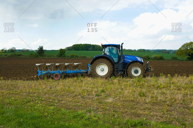 A tractor harrowing, ploughing in the stubble in a field.