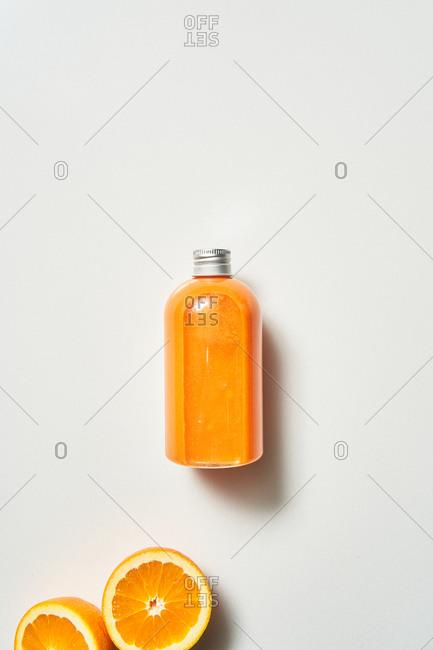Fresh squeezed orange juice and oranges on white background