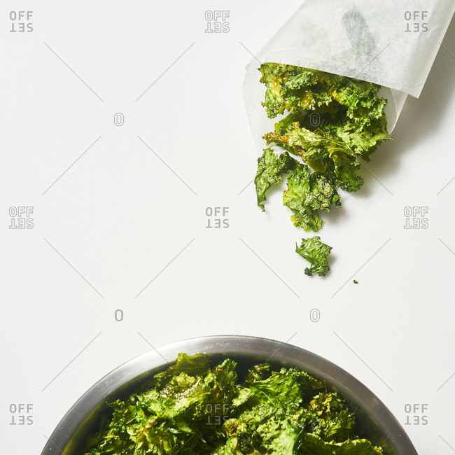 Pieces of lettuce with parchment paper and salad bowl on white background