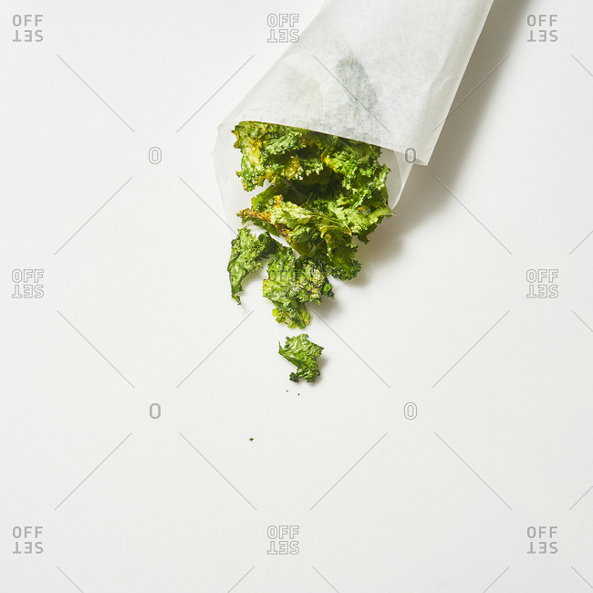Pieces of lettuce with parchment paper on white background