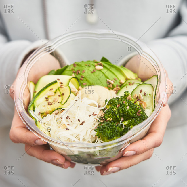 Woman holding a green salad with avocado, broccoli, sesame seeds, cucumber and cheese in a clear container